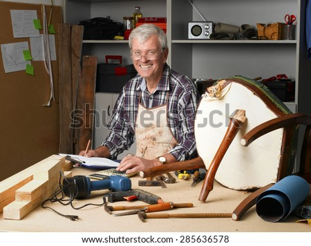 Portrait of senior carpenter holding and pointing clipboard in his hands while sitting at his workshop and repair the broken legged chair. Small business. - stock photo