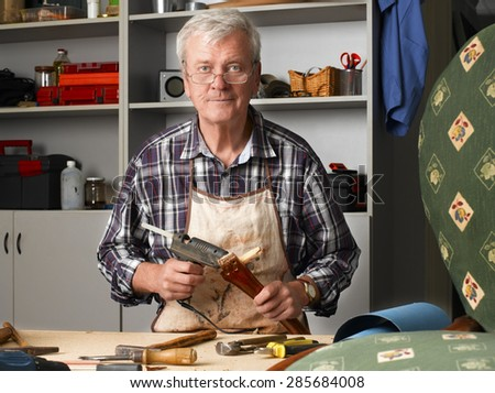 Portrait of senior carpenter sitting at his workshop and repair the broken legged chair. Small business.  - stock photo