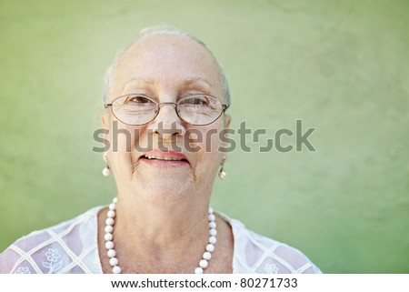 portrait of senior caucasian woman looking at camera against green wall and smiling. Horizontal shape, copy space - stock photo