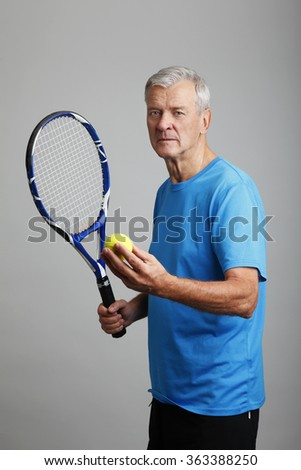 Portrait of senior coach holding in his hand a tennis racket and a tennis ball while standing against isolated background. - stock photo