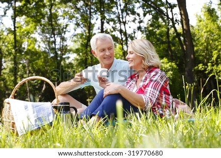 Portrait of senior couple chilling out in the forest. Elderly man and senior woman sitting on the blanket and talking while drinking a cup of tea.