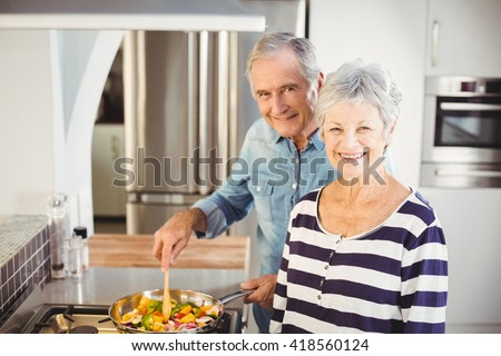 Portrait of senior couple cooking food in kitchen - stock photo