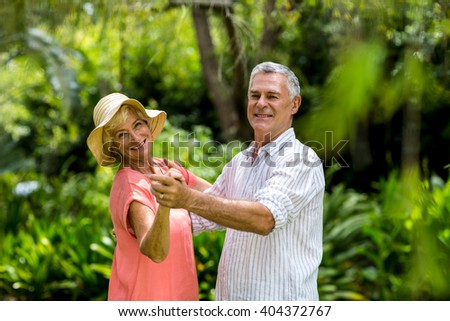 Portrait of senior couple dancing in yard