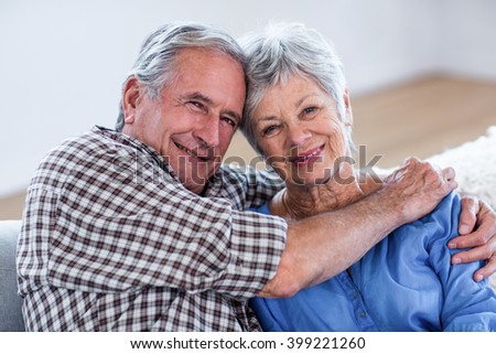 Portrait of senior couple embracing each other at home - stock photo