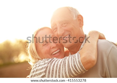 Portrait of senior couple embracing each other in countryside. - stock photo