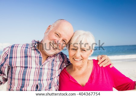 Portrait of senior couple embracing on the beach - stock photo