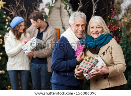 Portrait of senior couple holding Christmas presents with children standing in background at store - stock photo