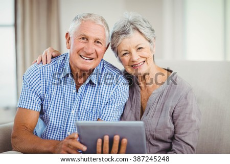 Portrait of senior couple holding digital tablet and smiling while sitting on sofa in living room - stock photo