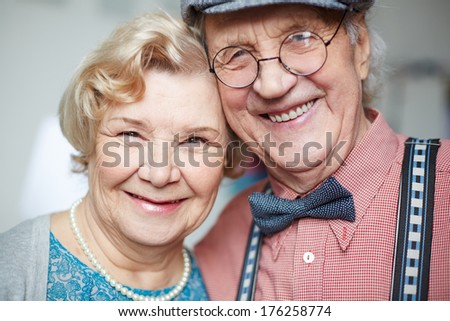 Portrait of senior couple in smart clothes looking at camera - stock photo