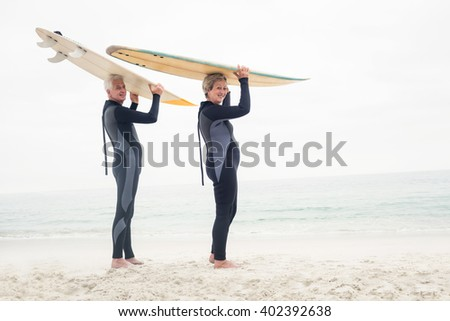 Portrait of senior couple in wetsuit carrying surfboard over head on the beach - stock photo