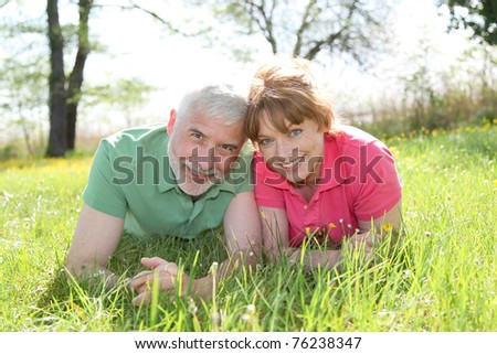 Portrait of senior couple laying in grass - stock photo