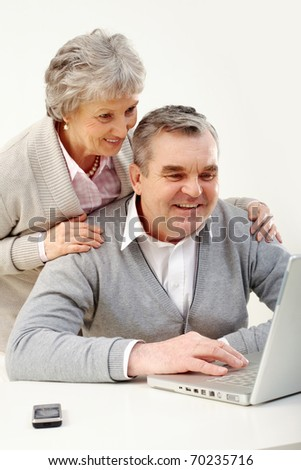 Portrait of senior couple looking at screen of laptop