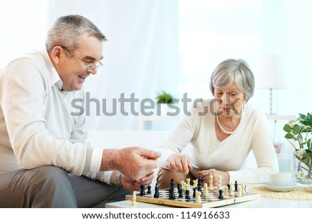 Portrait of senior couple playing chess at leisure