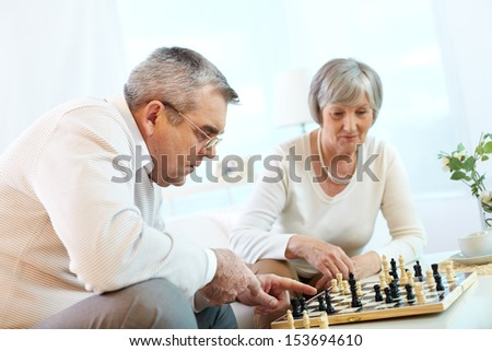 Portrait of senior couple playing chess at leisure  - stock photo