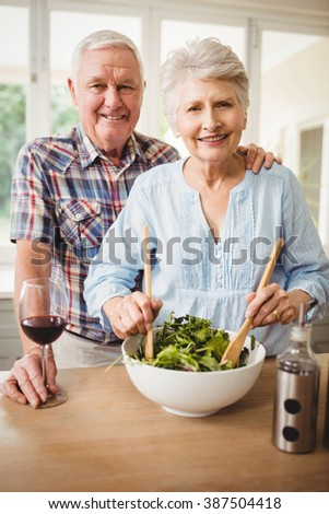 Portrait of senior couple preparing salad in kitchen - stock photo