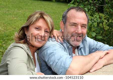 Portrait of senior couple relaxing in garden - stock photo