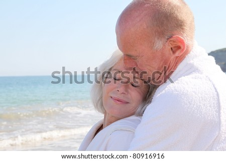 Portrait of senior couple relaxing on a resort beach - stock photo