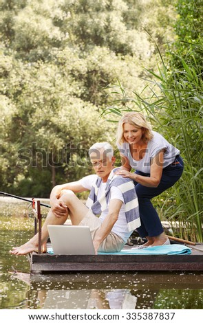 Portrait of senior couple relaxing together. Old man and elderly woman using laptop while they fishing at lakeside.