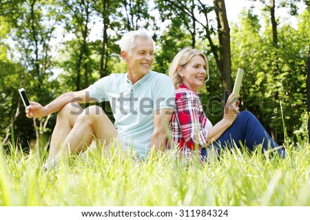 Portrait of senior couple sitting at the forest facing each other. Elderly woman holding hand digital tablet while senior man touching his mobile phone.