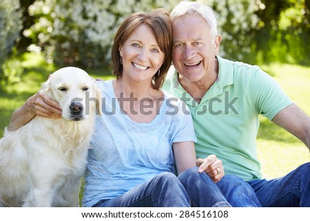 Portrait Of Senior Couple Sitting In Garden With Dog - stock photo
