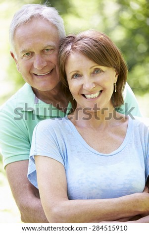 Portrait Of Senior Couple Sitting In Summer Garden Together