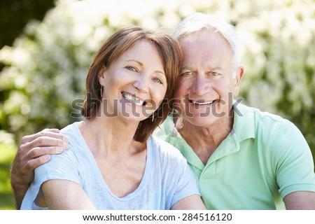 Portrait Of Senior Couple Sitting In Summer Garden Together - stock photo