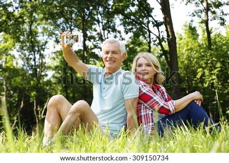 Portrait of senior couple taking selfies with smartphone while they are sitting at the forest.