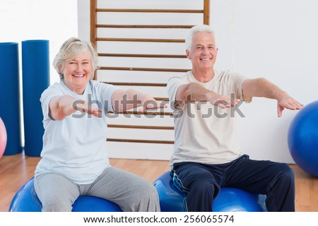 Portrait of senior couple with arms raised sitting on exercise ball at gym - stock photo