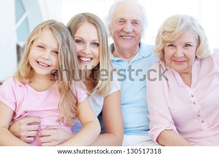 Portrait of senior couple with their daughter and granddaughter looking at camera - stock photo