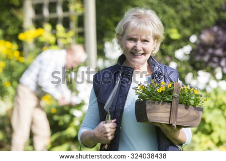 Portrait Of Senior Couple Working In Garden Together - stock photo