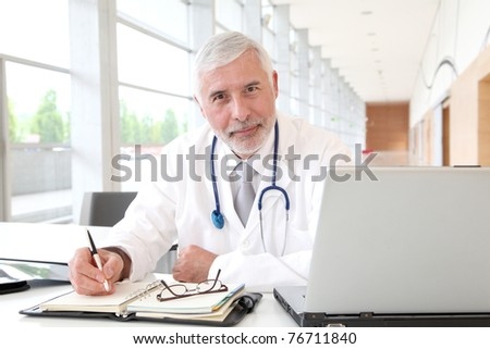 Portrait of senior doctor in office - stock photo