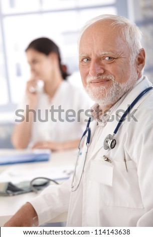 Portrait of senior doctor smiling at doctor's room. - stock photo