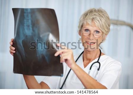 Portrait of senior female doctor holding hip Xray report in hospital - stock photo