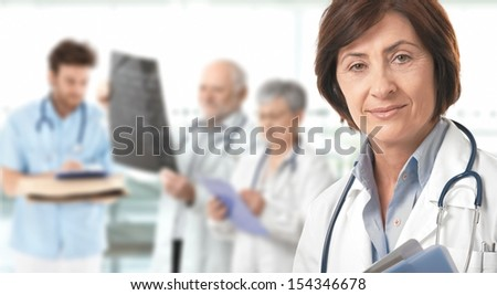 Portrait of senior female doctor looking at camera, medical team working in background.