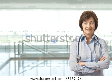 Portrait of senior female doctor on hospital corridor looking at camera smiling. Copy space on left.? - stock photo