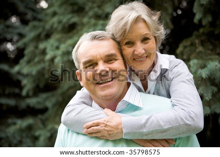 Portrait of senior female embracing her husband while he laughing and both looking at camera - stock photo