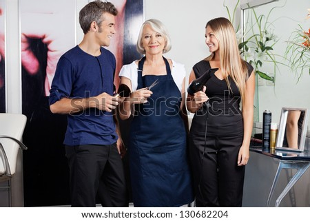 Portrait of senior female hairstylists holding scissors while colleagues with brush and dryer in salon - stock photo