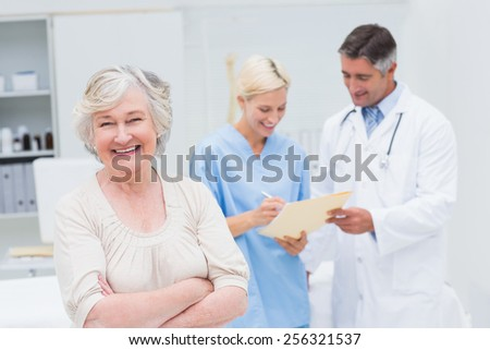 Portrait of senior female patient smiling while doctor and nurse discussing in background at clinic