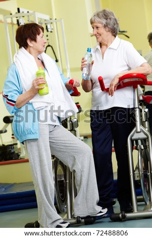 Portrait of senior females refreshing after workout in gym