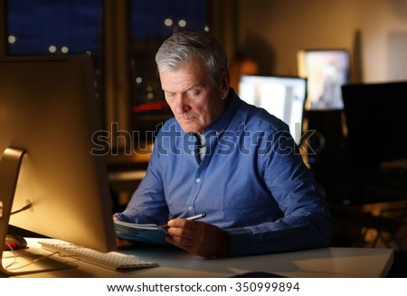 Portrait of senior financial advisor sitting at office and working late. Busy businessman holding in hand documents while analyzing data on computer.  - stock photo