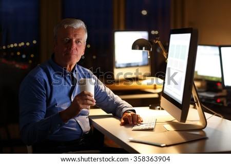 Portrait of senior financial advisor sitting at workplace in front of computer at late night and drinking coffee while analyzing data.