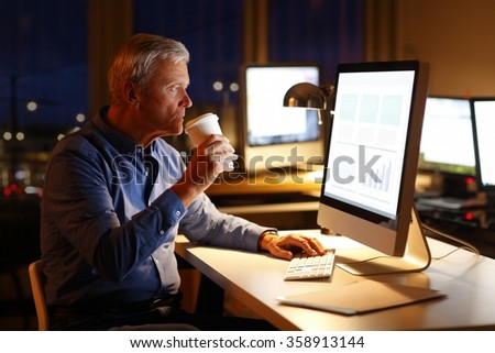 Portrait of senior financial advisor sitting at workplace in front of computer at late night and drinking coffee while analyzing data. - stock photo