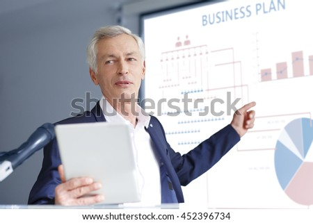 Portrait of senior financial director giving speech and presenting his new business plan.  - stock photo
