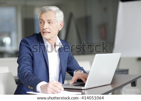 Portrait of senior financial man working on laptop at office.