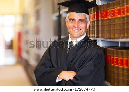 portrait of senior graduate with arms crossed in library - stock photo