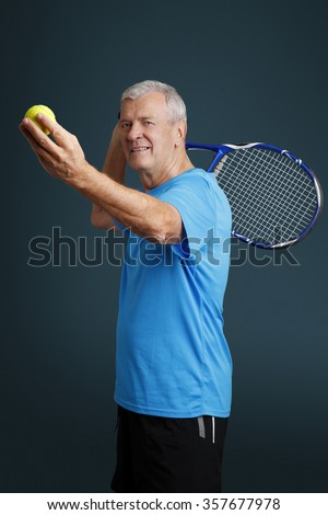 Portrait of senior holding in hand a tennis racket and tennis ball while making serve.  - stock photo