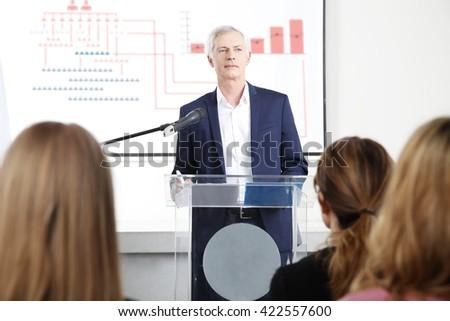 Portrait of senior investment adviser giving presentation on business meeting. - stock photo