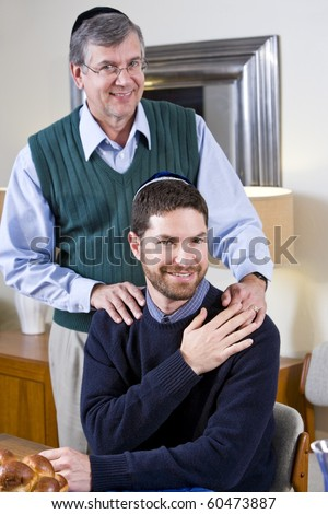 Portrait of senior Jewish man with adult son wearing yarmulkes - stock photo