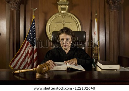 Portrait of senior judge holding book in courtroom - stock photo