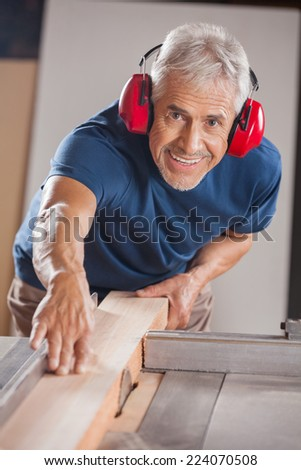 Portrait of senior male carpenter cutting wood with tablesaw in workshop - stock photo